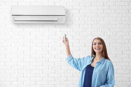 Young woman switching on air conditioner against brick wall background