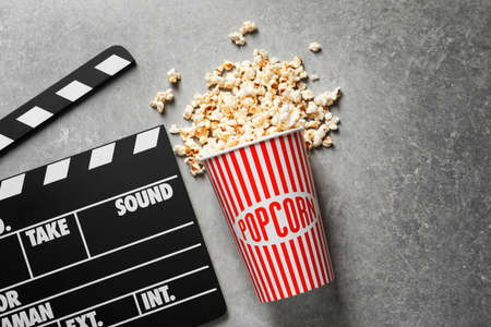 Clapperboard and popcorn on table Stock Photo
