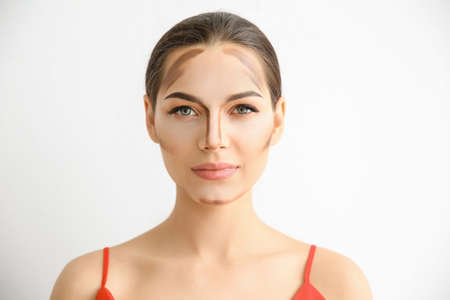 Young woman with contouring lines on her face against light background. Professional makeup products