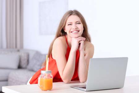 Woman using laptop indoors Stock Photo