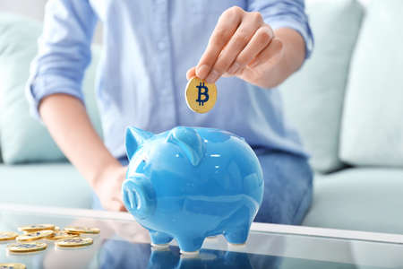 Woman putting golden bitcoin into piggy bank indoors