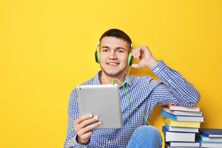 Man listening to audiobook through headphones on color background