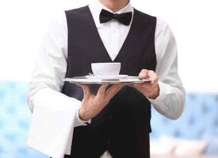 Waiter holding tray with cup of coffee indoors