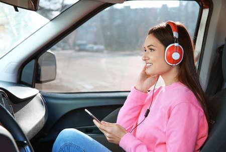 Woman listening to audiobook through headphones in car