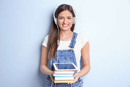 Woman listening to audiobook through headphones on color background Stockfoto