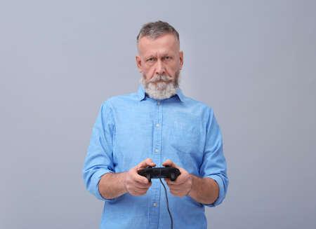 Emotional senior man playing video game on grey background Stock Photo
