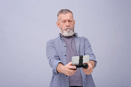 Emotional senior man with video game controller for smartphone on grey background