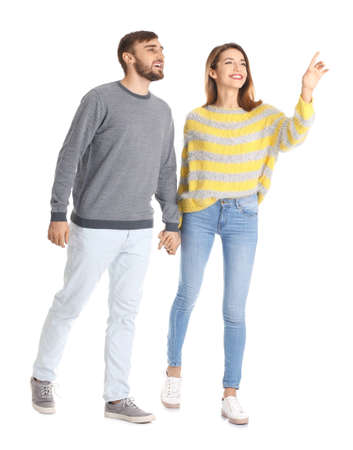 Young couple in casual clothes walking on white background