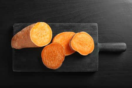 Sliced sweet potatoes on wooden board