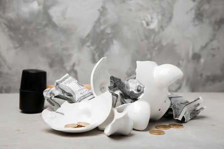 Broken piggy bank with money and sledgehammer on table
