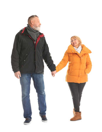 Mature couple in warm clothes walking on white background