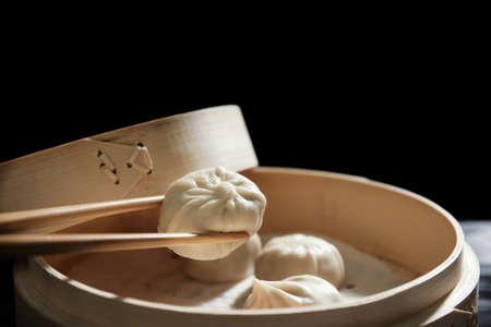 Holding baozi dumpling with chopsticks near bamboo steamer, closeup 写真素材