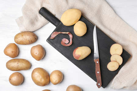 Composition with raw potatoes on wooden table
