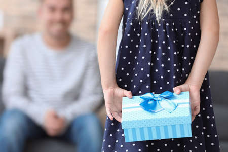 Cute little girl holding gift for father behind her back, closeup Stock Photo