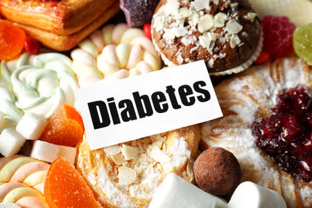 Card with word DIABETES and sweets, closeup