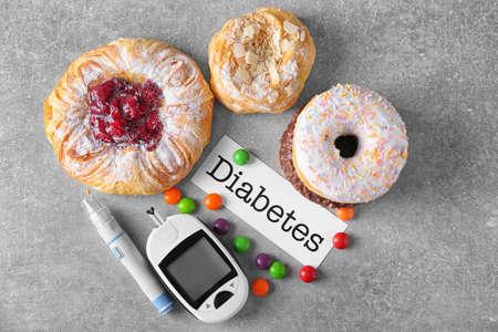 """디지털 혈당 측정기, 단어 """"당뇨병""""및 과자 테이블에 카드"""