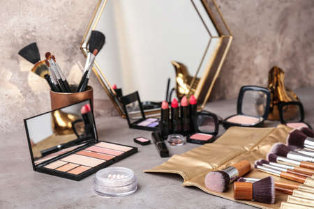 Decorative cosmetics and brushes of professional makeup artist on grey table