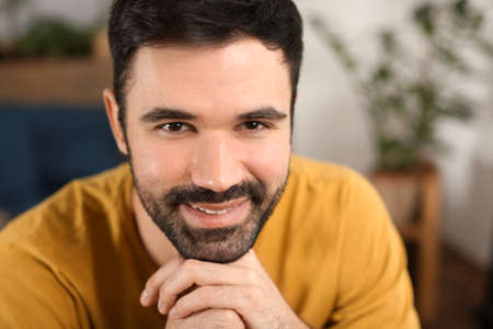 Young bearded man in casual clothes indoors Stock Photo