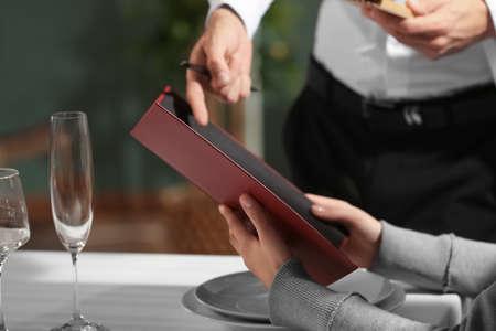 Waiter showing menu to client in restaurant