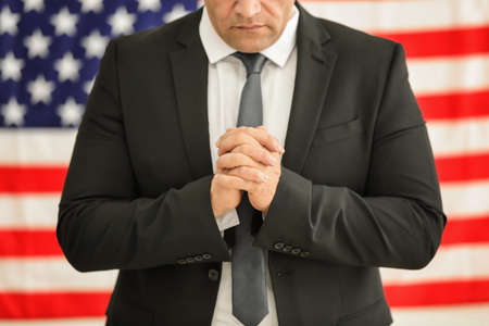 Man in suit praying on American flag background