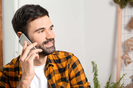 Young man talking on mobile phone indoors