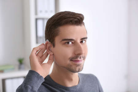 Young man with hearing aid indoors