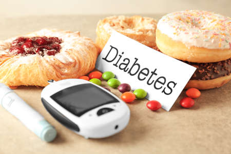 Digital glucometer, card with word Diabetes and sweets on table