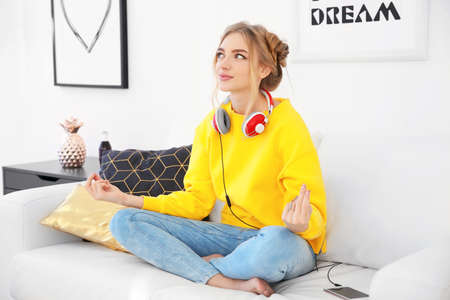 Attractive hipster girl meditating indoors