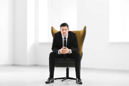 Handsome businessman sitting in comfortable armchair indoors Фото со стока - 100276566