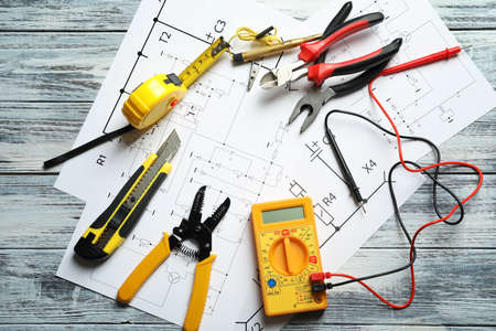 Different electrical tools and circuit diagram on wooden background Stock Photo