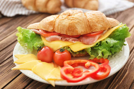 Plate with delicious croissant sandwich on wooden table Archivio Fotografico
