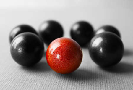 One brown ball among black ones on table. Difference and uniqueness concept Stock Photo