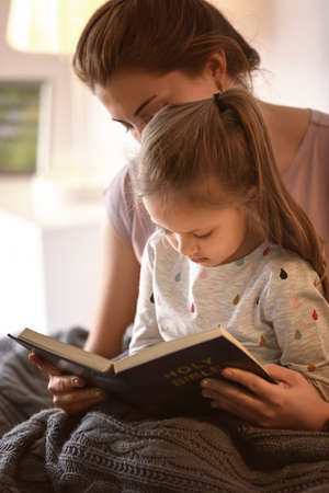 Religious Christian girl reading Bible with mother indoors