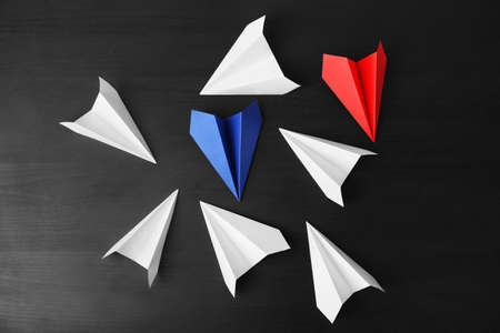 Blue and red paper planes among white ones on dark background. Difference and uniqueness concept Stock Photo