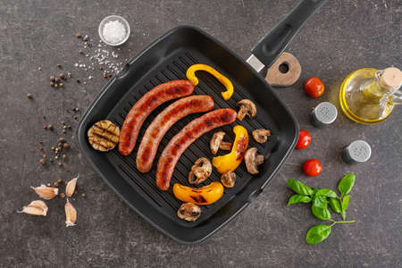 Grill pan with delicious sausages and vegetables on grey background