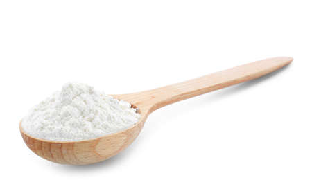Wheat flour in wooden spoon on white background
