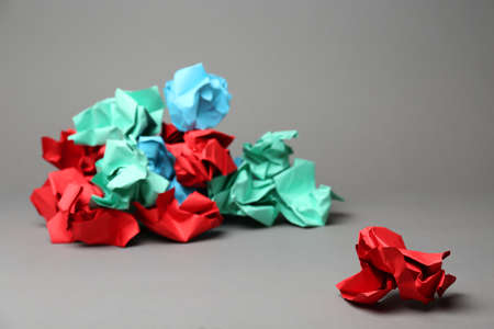 Crumpled paper ball near pile of different ones on grey background. Difference concept