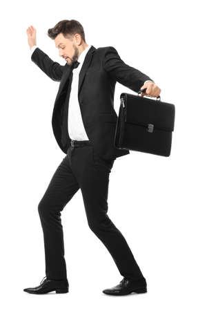 Young businessman with briefcase balancing on white background