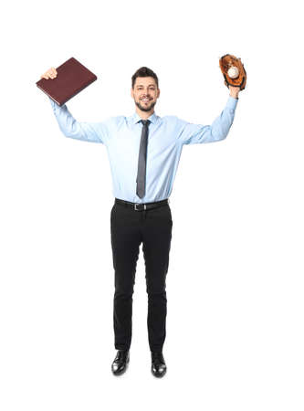 Young businessman holding notebook and baseball glove with ball on white background