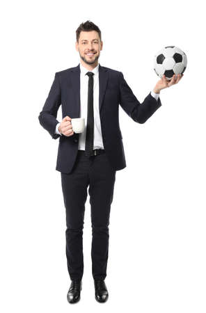 Young businessman with cup of coffee and soccer ball on white background