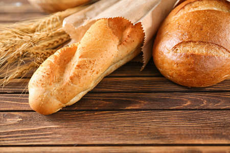 Different tasty bread on wooden table Stock Photo