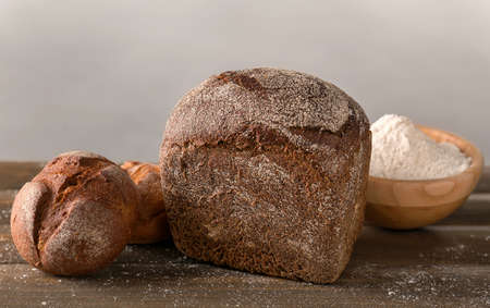 Fresh tasty bread on wooden table against light background