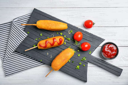 Tasty corn dogs with ketchup on wooden board