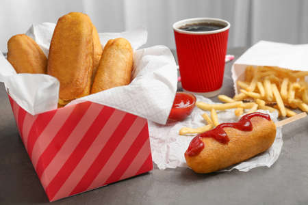 Tasty corn dogs with ketchup on table