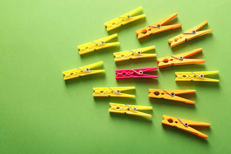Clothes pegs and one different on color background Stock Photo
