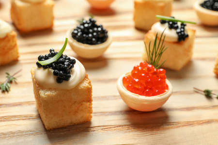 Delicious canapes with black and red caviar on wooden table Stock Photo