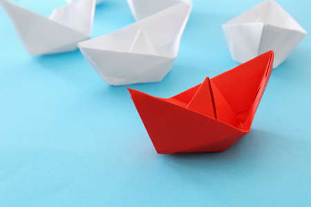 Paper ships and one different on color background Stock Photo