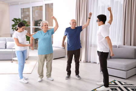 Senior people doing exercises with caregivers at home