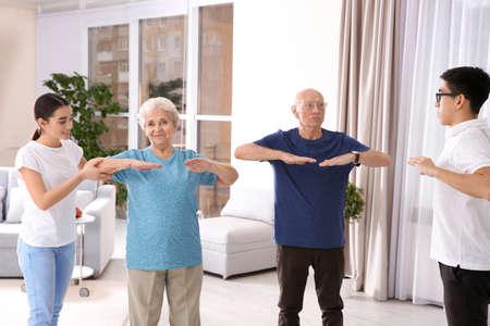 Gente senior che fa gli esercizi con i caregivers a casa