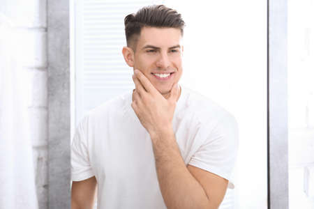 Handsome man after shaving near mirror in bathroom